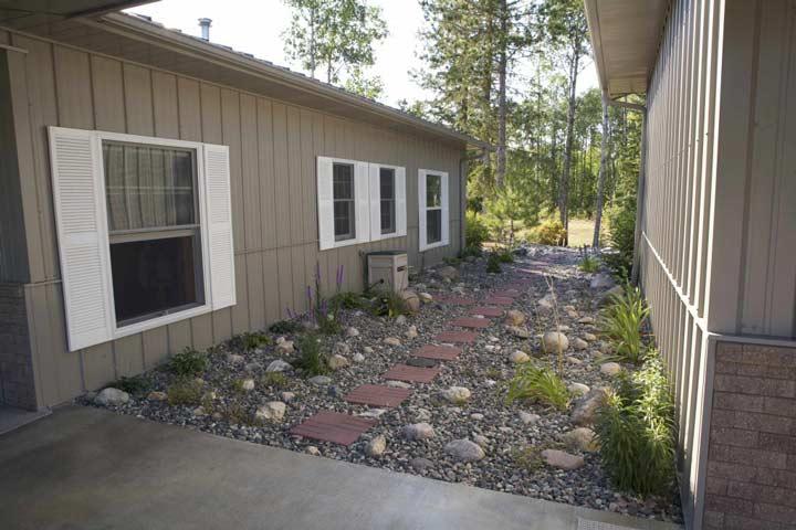 Quaint garden space separates house from garage.