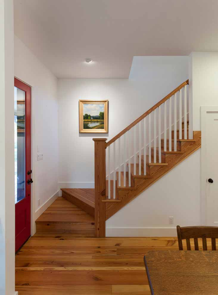 Wooden stairs, to the left of the front door, leads to the second floor. The door under the stairs may open to a storage area or the toilet.