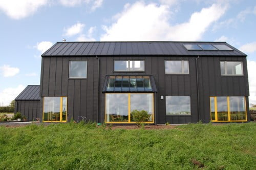 The large windows in bright yellow frames give the property a distinct character