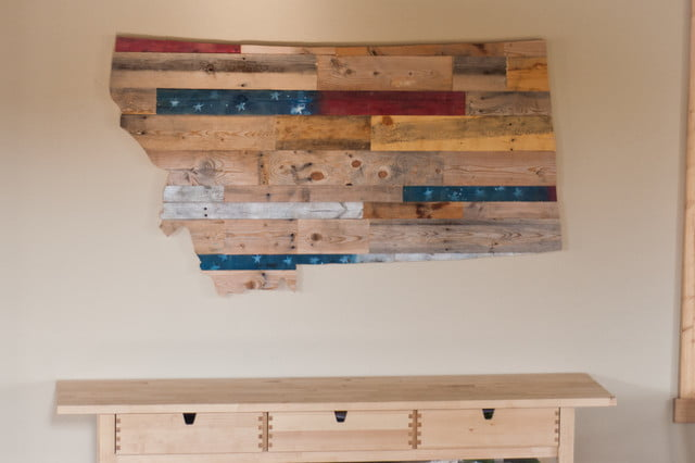 A wood design map of the U.S.A. above a wooden desk. Very rustic and pleasing to the eye. One way of merging wood decor to a metal structure.