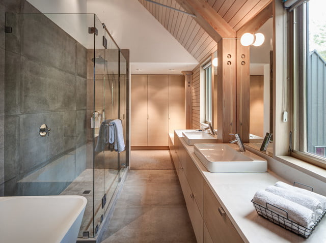 View of sophisticated wash room with glass shower doors.