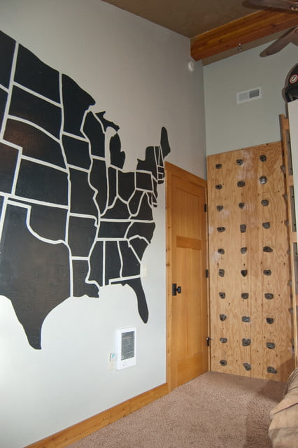 A gorgeous stenciled map design on one wall and a climbing wall on the other.