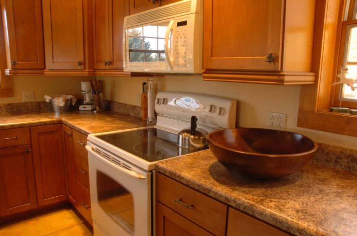 The kitchen is a combination of wooden cupboards and granite and marble counter tops.