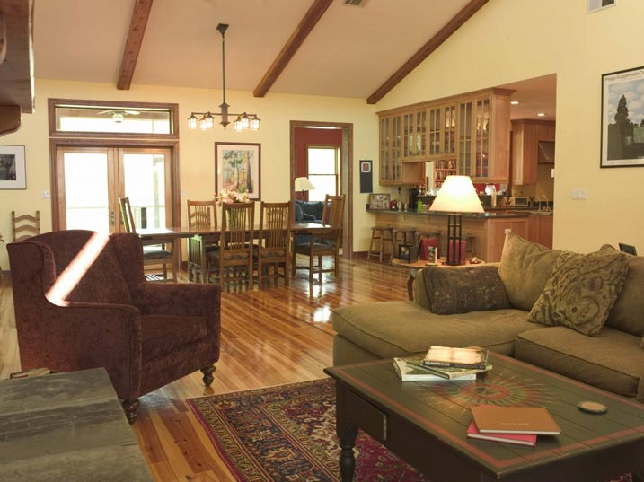 The living room, dining room, and kitchen sharing one open space. Another room is located behind the open door. Double doors in the picture lead to the outside of the house.