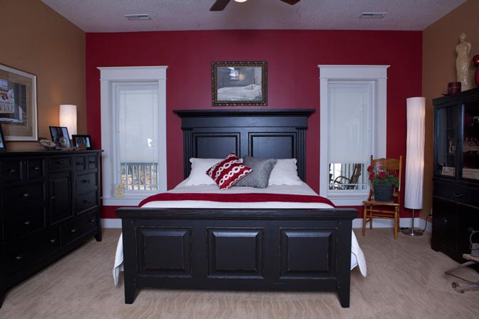 The master suite. A room that exudes elegance. The dark color of the bed frame makes the bed the focal point of the picture.