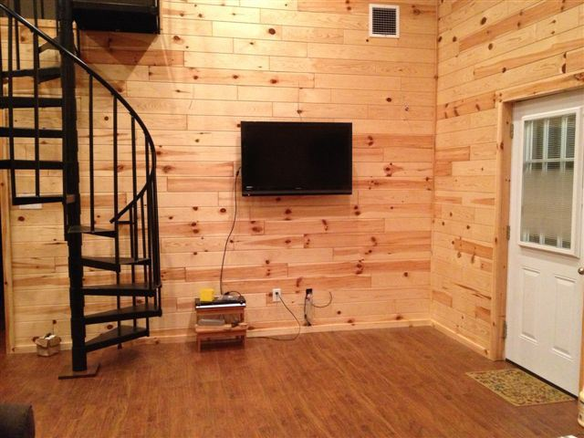 A flat screen TV is attached to the wall  to maximize space.