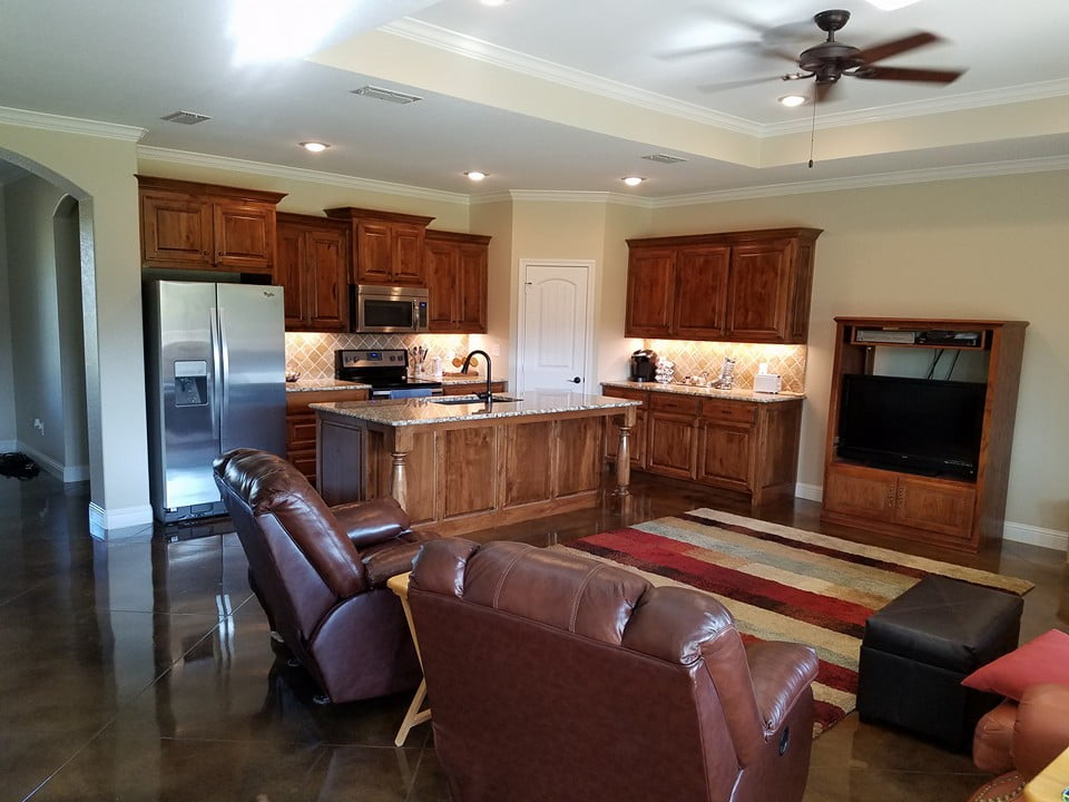 The brown leather sofas and custom cabinets in the living room is perfect for the cream colored theme in the interior.