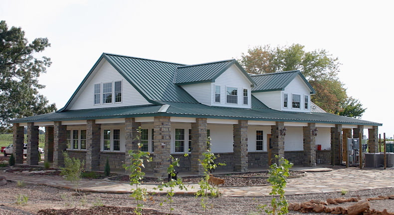 kodiak steel frame home with white siding and green metal roof with stone wainscot columns